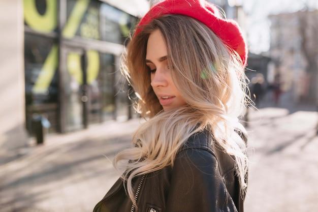 長いブロンドの髪と赤い帽子をかぶった魅力的なスタイリッシュな女性のクローズアップの肖像画は、街で彼女の目を閉じて笑顔