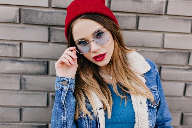 그녀의 파란 안경을 만지고 관심을 표현하는 매력적인 백인 여자의 클로즈업 초상화. 데님 재킷에 심각한 아름 다운 여자의 야외 사진.