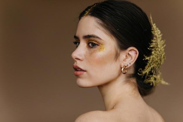 매력적인 여자의 클로즈업 초상화는 황금 귀걸이를 착용합니다. 머리에 식물을 가진 귀여운 갈색 머리 소녀.