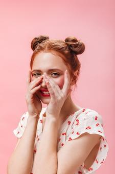 노란색 눈 그림자와 함께 매력적인 여자의 클로즈업 초상화. 흰색 블라우스 귀여운 분홍색 배경에 웃는 여자.
