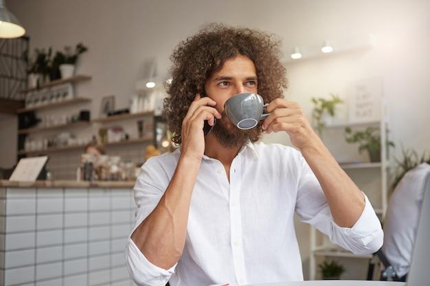 Крупным планом портрет очаровательного молодого мужчины позирует над интерьером кафе, пить кофе во время разговора по телефону, глядя в окно со спокойным лицом