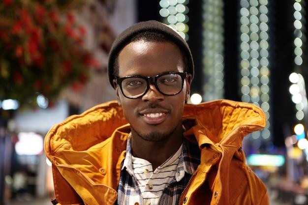 Крупным планом портрет веселый и счастливый молодой темнокожий мужчина турист, одетый в зимнее пальто, очки и шляпу, стоя на улицах современного мегаполиса в ночное время, ожидая такси за пределами аэропорта
