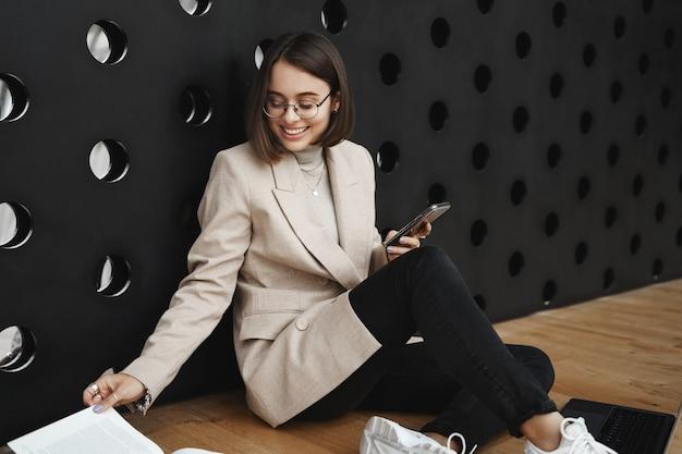 쾌활하고 매력적인 여성 학생, 소녀가 바닥 린 벽에 앉아 페이지를 넘기고 웃고, 공부하고, 보고서 또는 프로젝트를 준비하고, 휴대 전화를 사용하여 인터넷 정보를 검색하는 클로즈업 초상화.