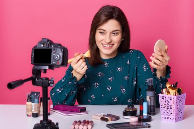 メイクアップのためのプロのブラシを保持しているスタジオでピンクの上に孤立したポーズ陽気な美容ブロガーの肖像画を間近します。