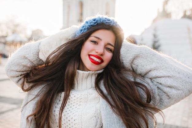 ぼかし市の冬の朝にポーズをとって長い黒髪の陽気な女の子のクローズアップの肖像画。寒い日に写真撮影を楽しむ青いベレー帽のブルネットの女性。