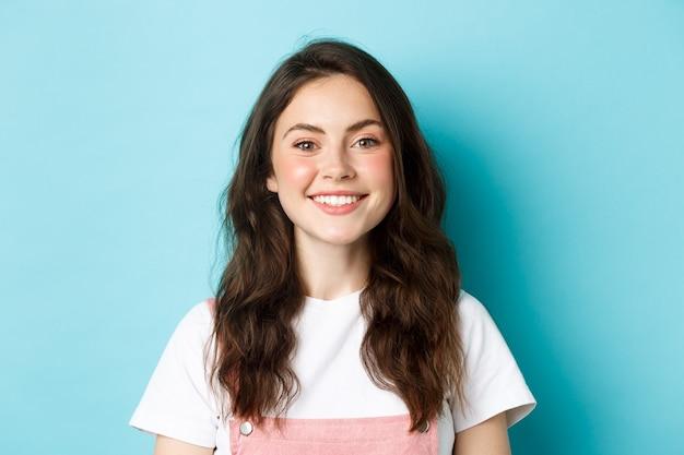 Крупным планом портрет веселой гламурной девушки с милым макияжем, улыбающимися белыми зубами и счастливыми, глядя на камеру, стоя на синем фоне.