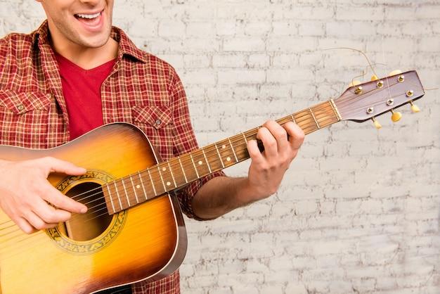 Крупным планом портрет веселого человека, играющего на гитаре и поющего