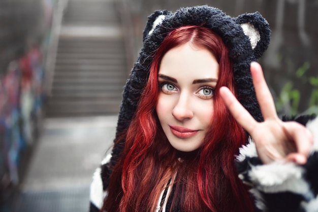 평화 서명과 미소를 몸짓으로 빨간 머리를 가진 쾌활한 장난 힙 스터 십대 소녀의 초상화를 닫습니다