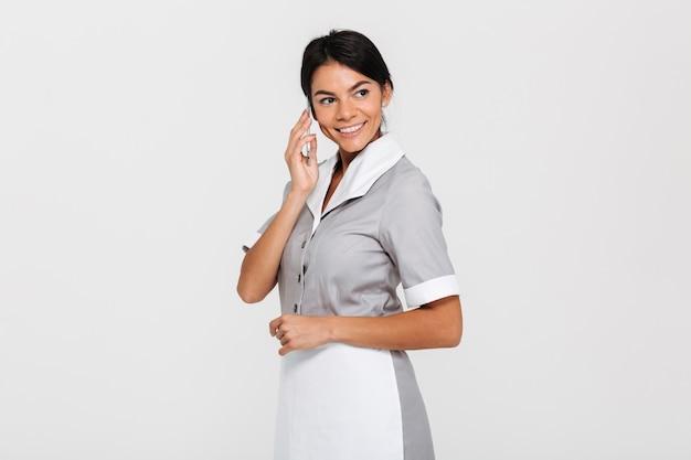 携帯電話で話している灰色の制服を着た陽気なきれいな女性のクローズアップの肖像画