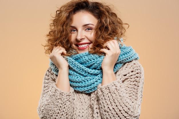 베이지 색 벽에 니트 스웨터와 회색 neckwarmer에 밝은 미소 아름다운 갈색 머리 곱슬 소녀의 초상화를 닫습니다