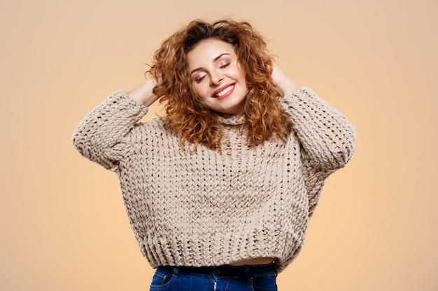 Крупным планом портрет веселой улыбающейся красивой брюнетки кудрявой девушки в вязаном свитере на бежевой стене