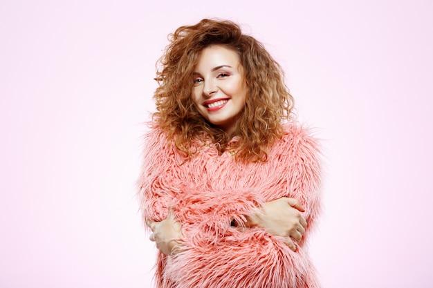 흰 벽에 분홍색 모피 코트에 밝은 미소 아름다운 갈색 머리 곱슬 소녀의 초상화를 닫습니다
