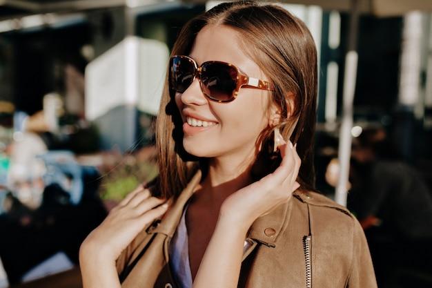 ぼやけた背景で彼女の髪に触れてメガネで陽気な白人女性のクローズアップの肖像画。素敵な笑顔のきれいな女性は外で時間を過ごし、良い気分を示しています