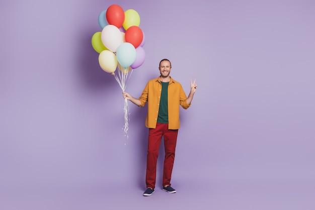 Крупным планом портрет веселого молодого человека празднуют день рождения держать воздушные шары на фиолетовой стене