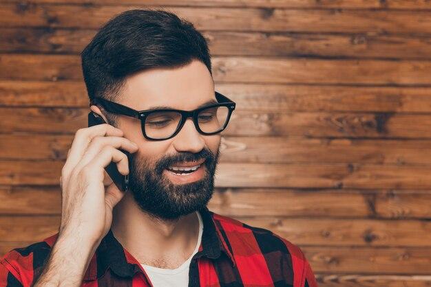 セルで話している眼鏡の陽気な若い男の肖像画をクローズアップ