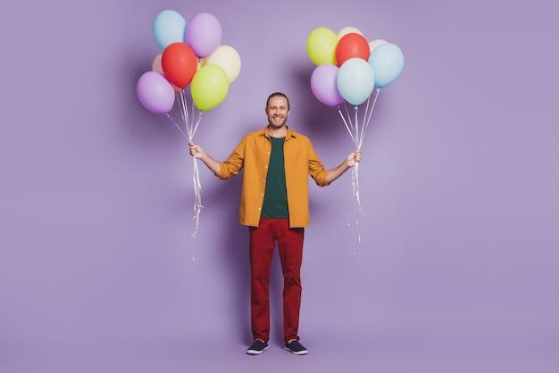 Крупным планом портрет веселого молодого человека партии гостя держать воздушные шары на фиолетовой стене