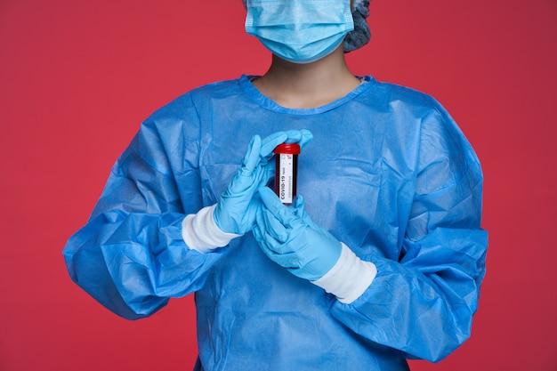 Закройте вверх по портрету доктора китайской женщины в специальном костюме держа пробирку с пробой крови. covid-19 положительный тест. на красном фоне
