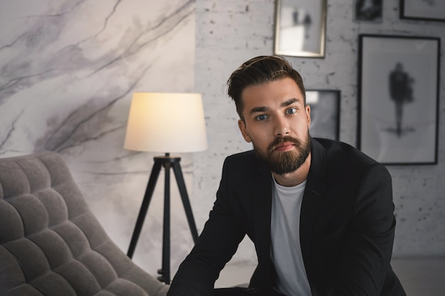 Крупным планом портрет уверенно привлекательного модного молодого бизнесмена с подстриженной бородой и модной прической, позирующего в современном уютном интерьере, одетого в формальный стильный костюм,