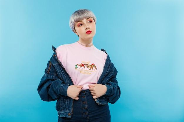 Крупным планом портрет уверенно красивая кукольная девушка с короткими светло-фиолетовыми волосами в повседневной уличной джинсовой куртке над синей стеной