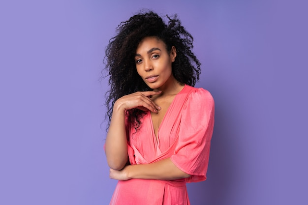 紫色の壁の上に立っているピンクのドレスの巻き毛の髪型で自信を持って混血の女性の肖像画を閉じます。