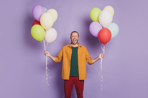 Крупным планом портрет сумасшедшего в стиле фанк гость вечеринки держит воздушные шары на фиолетовой стене