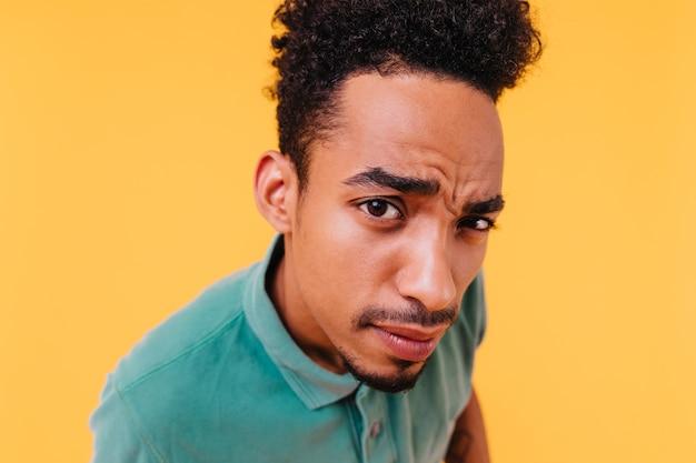 黒髪の好奇心旺盛なアフリカ人のクローズアップの肖像画。分離されたブルネットの男性モデルの屋内ショット。