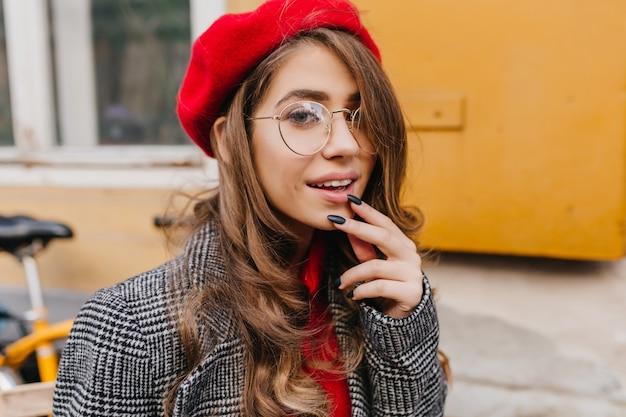 トレンディな赤いベレー帽の好奇心旺盛な白人女性のクローズアップの肖像画