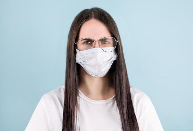 Макро портрет милой девушки носить белую рубашку защиты от гриппа холодную лицевую маску, изолированную на синем пастельном фоне с запотевшими очками.