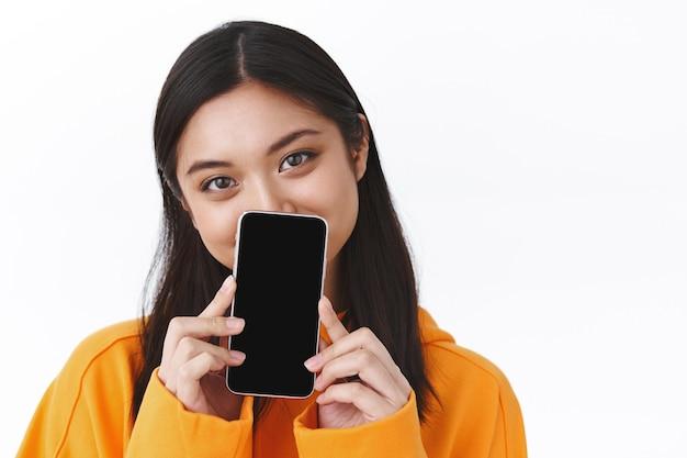 オレンジ色のパーカーでかわいいアジアの女の子のクローズアップの肖像画、スマートフォンの後ろに顔を隠し、携帯電話のディスプレイを表示し、目で笑って、アプリケーション、アプリのプロモーション、白い壁をお勧めします