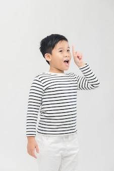 Крупным планом портрет милого мальчика, указывающего жестом пальца, изолированные на белом фоне
