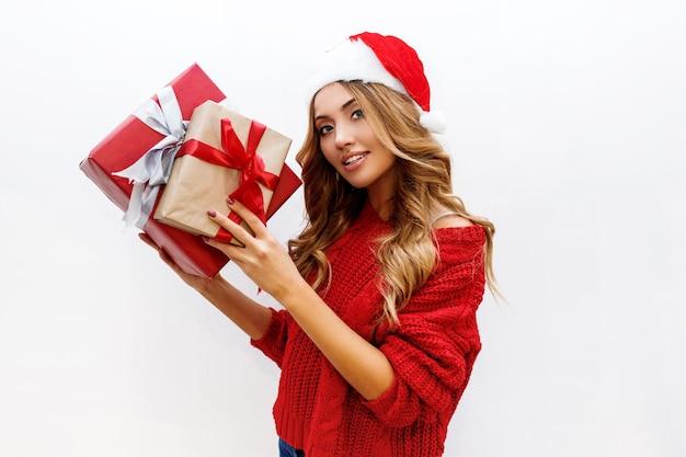 Закройте вверх по портрету милой беззаботной девушки с сияющими волнистыми светлыми волосами, позирующими с подарочной коробкой. в красной маскарадной шляпе санта-клауса и свитере.