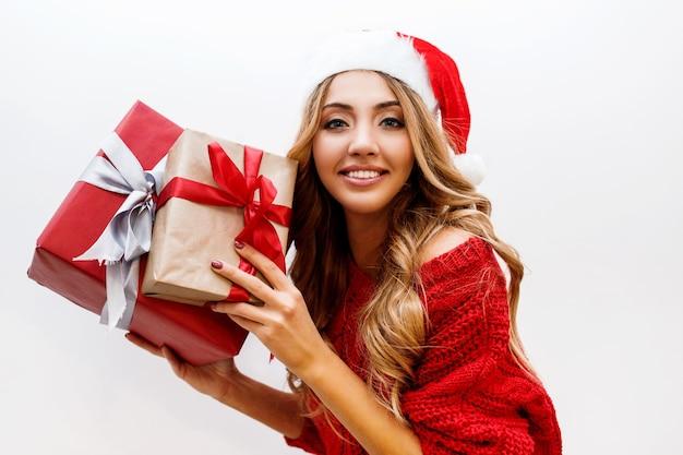 빛나는 물결 모양의 금발 머리 선물 상자와 함께 포즈와 귀여운 평온한 여자의 초상화를 닫습니다. 빨간 산타 가장 무도회 모자와 스웨터를 입고.