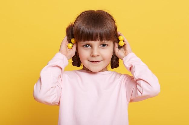 Крупным планом портрет милой, любопытной, умной, привлекательной маленькой девочки, касающейся ее косичек и делающей новую прическу, позирующей изолированной над желтой стеной.