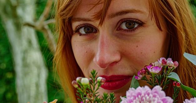 꽃과 함께 귀여운 여자 얼굴의 초상화를 닫습니다