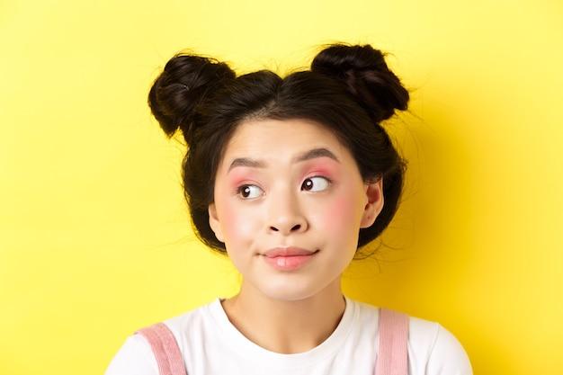 かわいいグラマーアジアの女の子、明るいメイクと髪型のクローズアップの肖像画、愚かな顔、黄色のロゴを脇に見て
