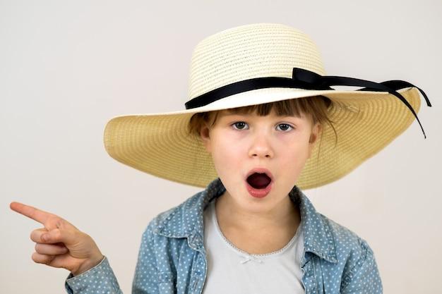 깜짝 감정을 가진 베이지색 모자를 쓴 귀여운 소녀의 초상화를 클로즈업하세요.