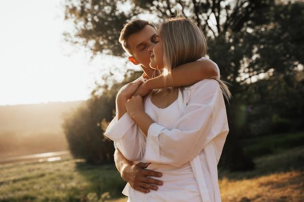 目を閉じてお互いを楽しんでいるかわいい素敵なカップルの肖像画を閉じます。男は頬にガールフレンドにキスします。