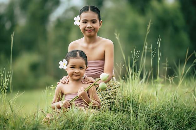 닫기, 태국 전통 드레스에 귀여운 여동생과 젊은 여동생의 초상화와 초원, 미소, 형제 사랑 개념, 복사 공간에 앉아 그녀의 귀에 흰 꽃을 넣어