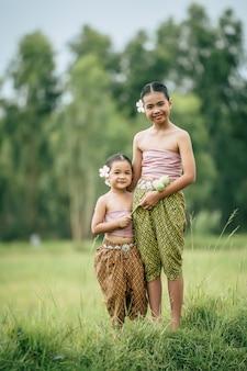 닫기, 태국 전통 드레스에 귀여운 여동생과 젊은 여동생의 초상화와 쌀 필드에 서있는 그녀의 귀에 흰 꽃을 넣어 미소, 형제 사랑 개념, 복사 공간
