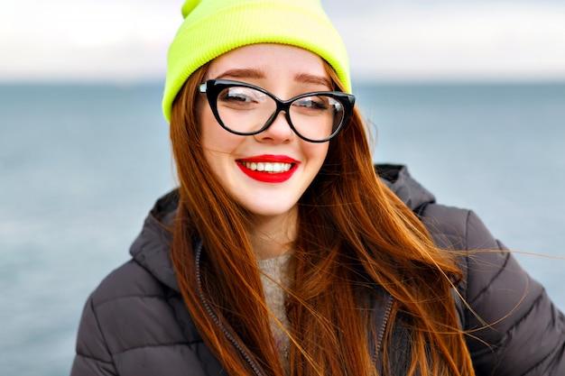 赤い髪のかわいい笑顔の陽気な女性、ビーチで素晴らしい時間を過ごして、冬の寒い時間、若い旅行者、明るいメイク、ネオンハット、暖かいジャケット、流行に敏感なメガネの肖像画を間近します。
