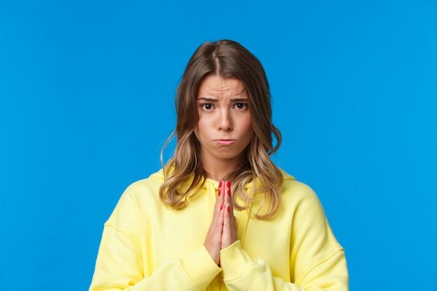 Портрет крупным планом милой угрюмой европейской женщины-блондинки, просящей о помощи, просящего об одолжении, действительно нужно что-то, держащего руки в молитве, хмурящегося и рыдающего, просящего прощения, голубая стена