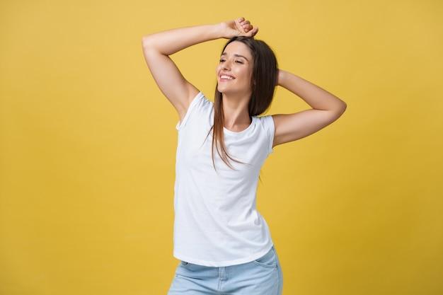 頭の後ろの手でリラックスしたかわいい若い女性のクローズアップの肖像画。黄色の背景の上に分離されました。