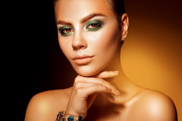 カメラを見て緑の色のメイクでキューティーな素敵な女性の肖像画をクローズアップ