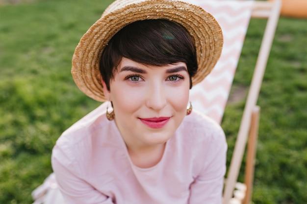 Макро портрет темноволосой улыбающейся девушки, сидящей на кресле и с интересом смотрящей