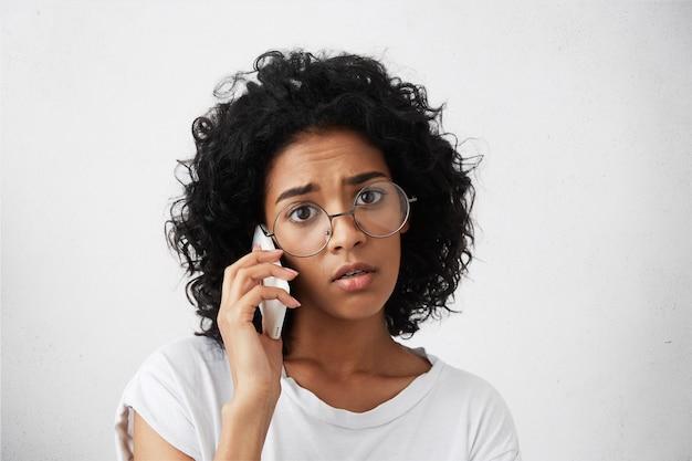 濃い豊かな髪を持つ浅黒い肌のアフロアメリカンの女性のクローズアップの肖像画
