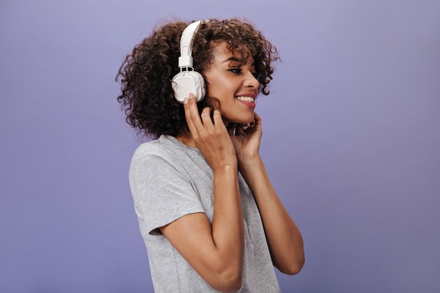 紫色の壁にヘッドフォンで浅黒い肌の女性のクローズアップの肖像画