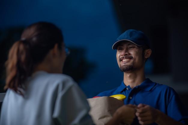 配達員の肖像画、青いtシャツの制服を着た笑顔の男、オンラインショッピングの食料品、新しい通常のライフスタイルコンセプト、小売店のeコマース、都市生活、配達輸送をクローズアップします。