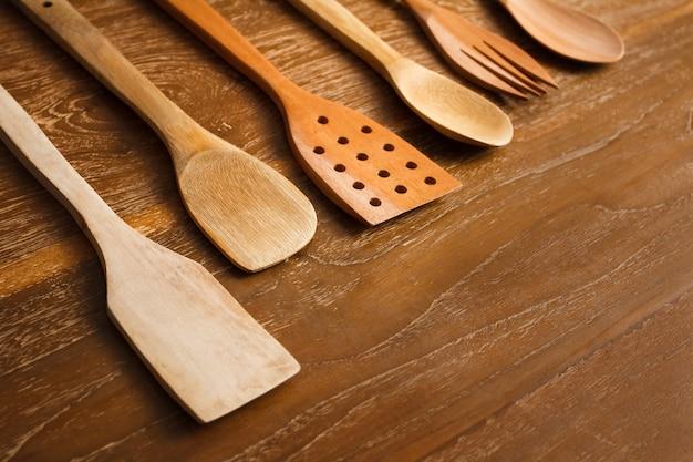 木製の背景にさまざまな木製のキッチンツールの肖像画を閉じる