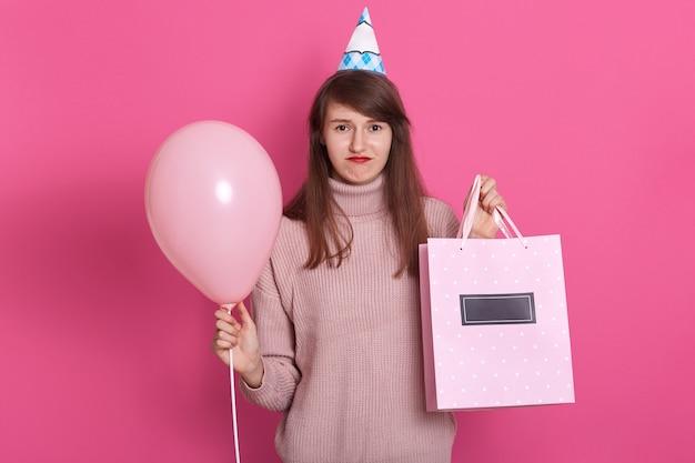 파티 모자와 트럼펫과 핑크 풍선 실망 어린 소녀의 초상화를 닫습니다