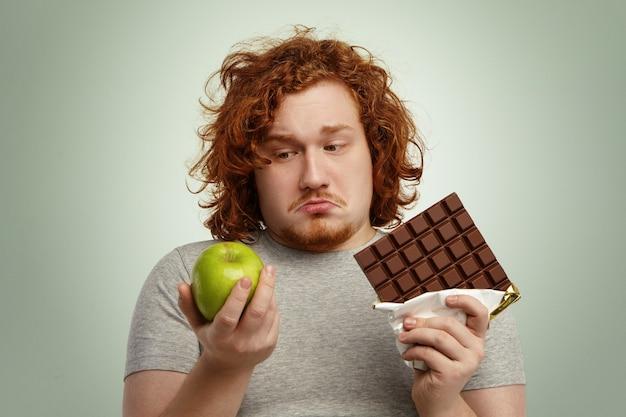 ジレンマに直面している疑わしい優柔不断の太りすぎの若い男性の肖像画を間近します。